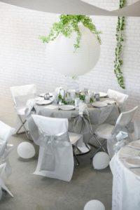 Partydekoration-mit-silbernen-Automatik-Stuhlschleifen-auf-weissen-Stuhlhussen